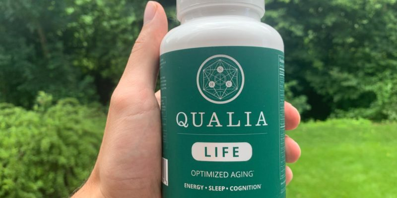A hand holding one bottle of Qualia Life