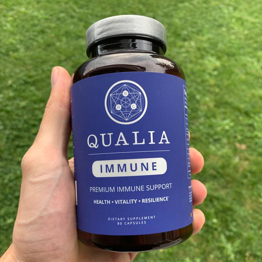 A hand holding a bottle of Qualia Immune