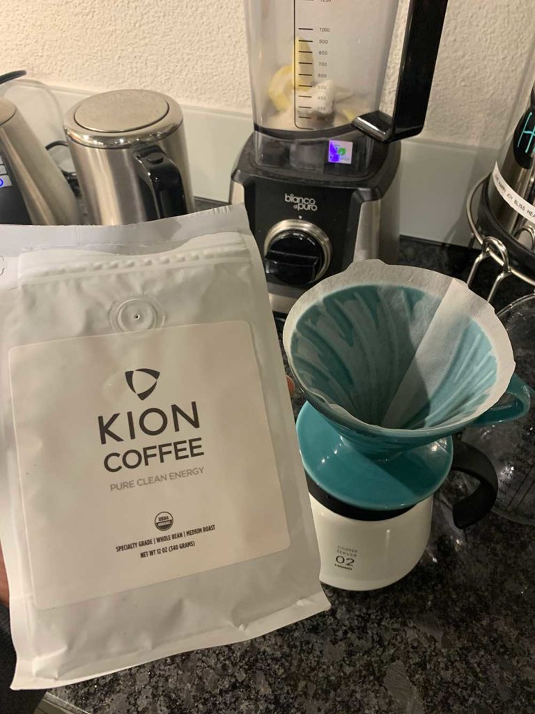 A bag of Kion Coffee infront of a Hario V60 coffee maker and a blender