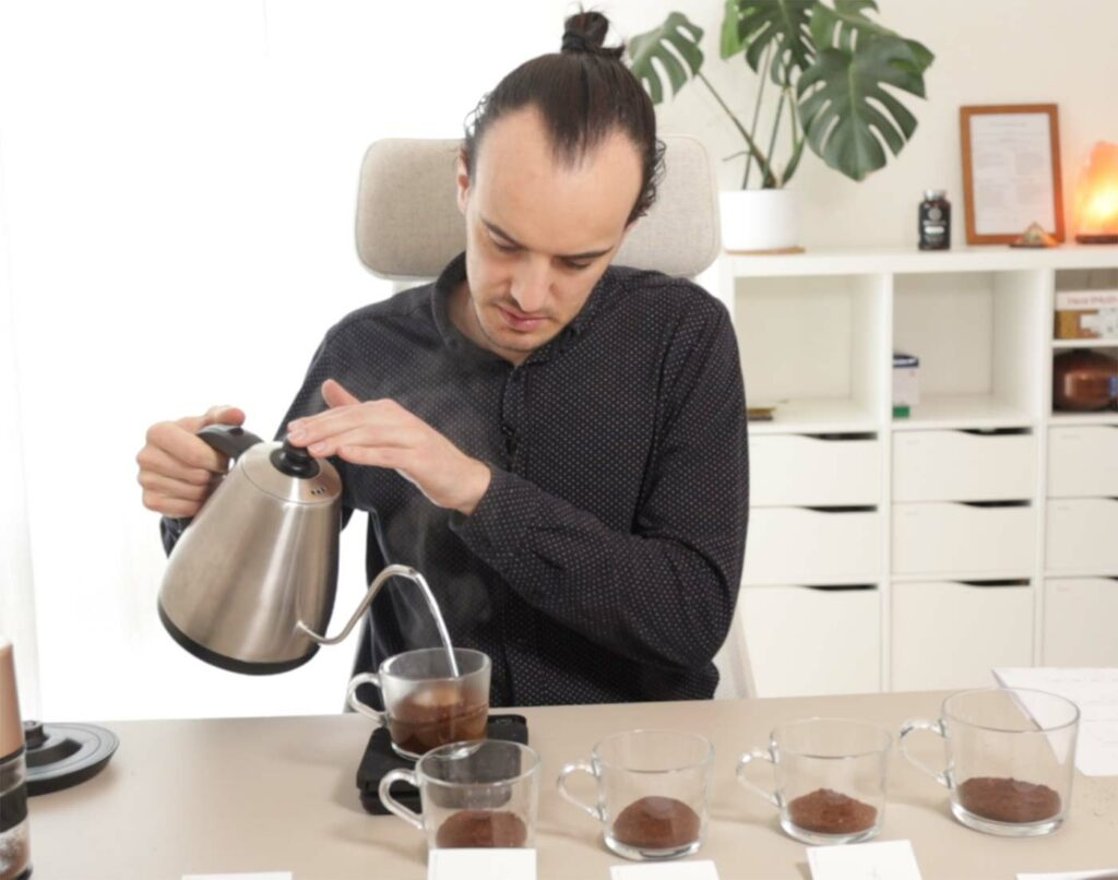Max pouring hot water into a cup of ground coffee at a table with 5 cupping cups