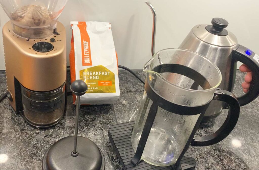 A bag of Bulletproof Breakfast Blend coffee next to a burr grinder, a gooseneck kettle and a French-press coffee maker