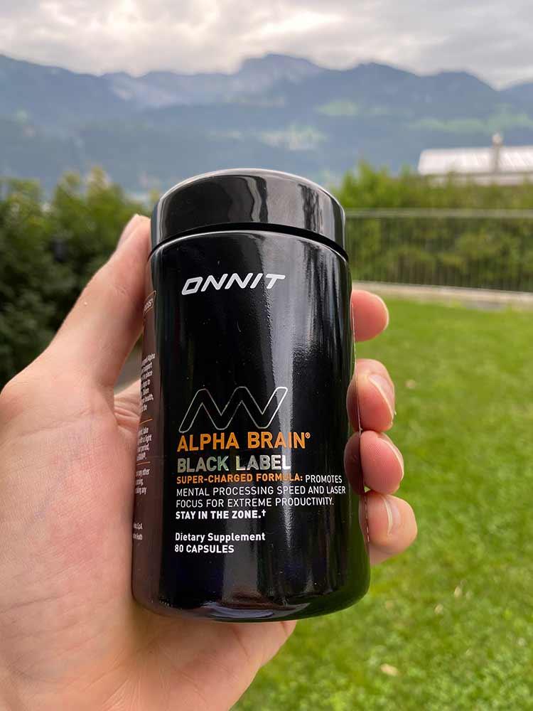A hand holding a bottle of Alpha Brain Black Label