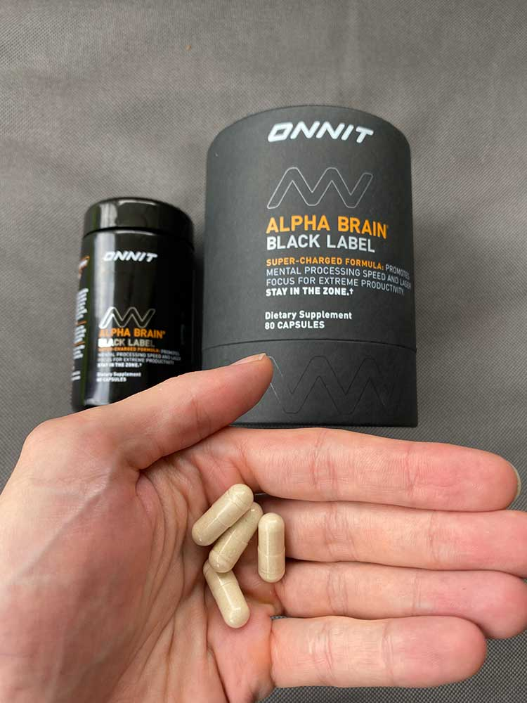 A hand holding 4 capsules of Alpha Brain Black Label infront of the Alpha Brain packaging and bottle